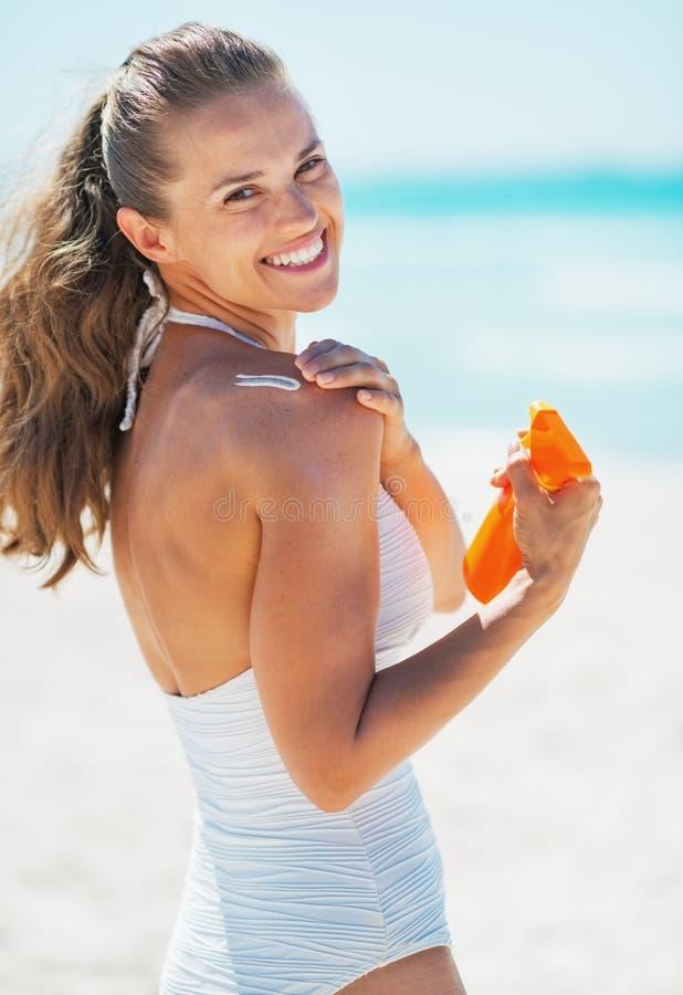应用太阳在海滩的愉快的少妇块奶油 库存图片
