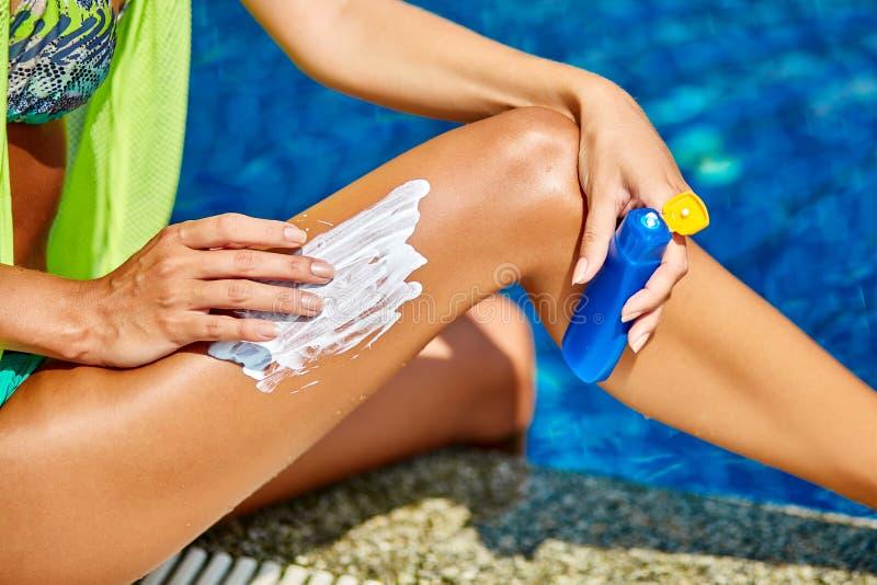 应用太阳在tann的比基尼泳装的美丽的愉快的妇女块奶油 免版税库存图片