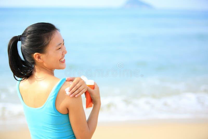 应用太阳块奶油身体的少妇 库存照片