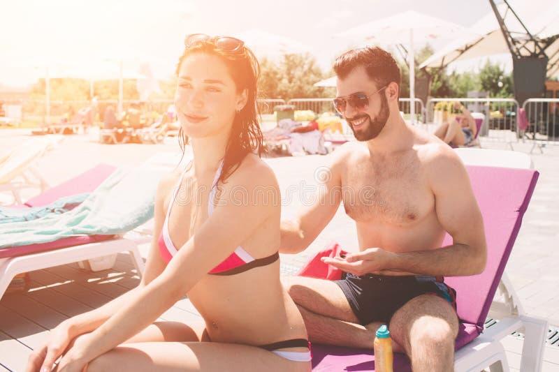 应用夫妇suncream 应用在女朋友` s后面的愉快的年轻人奶油 库存照片