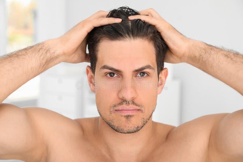 应用头发的帅哥在卫生间里 免版税库存图片