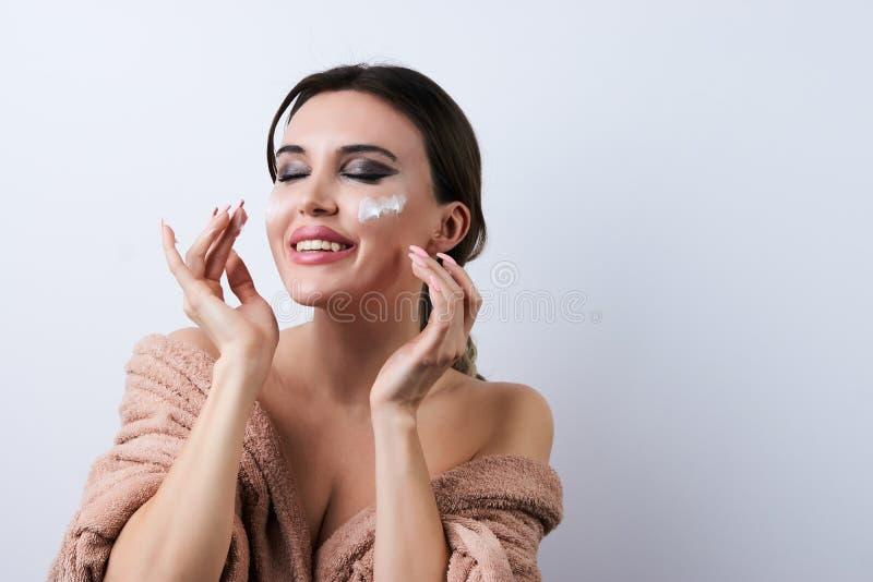 应用奶油在她的面孔,特写镜头的愉快的美丽的年轻女人 库存照片