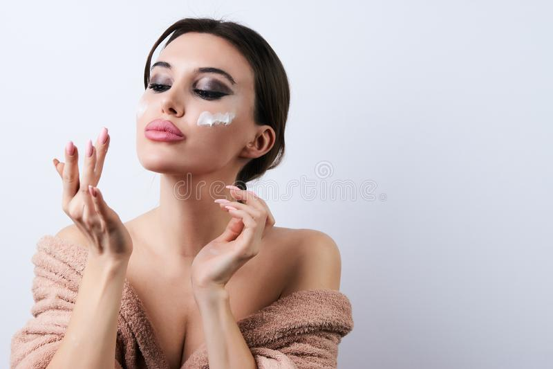 应用奶油在她的面孔,特写镜头的愉快的美丽的年轻女人 免版税图库摄影