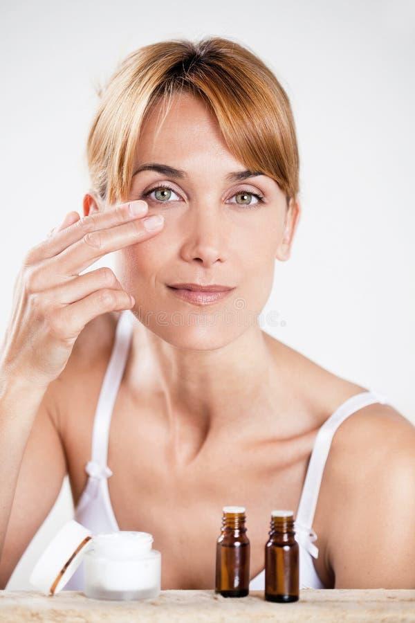 应用奶油的妇女在她的眼睛附近 免版税库存图片