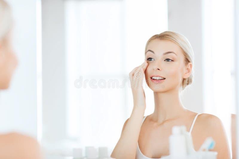 应用奶油的愉快的妇女于面孔在卫生间 免版税库存照片