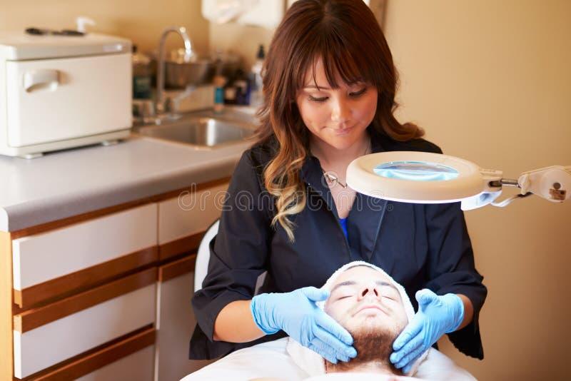 应用奶油的美容师于诊所的男性客户 库存图片