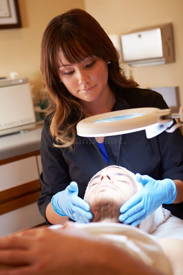 应用奶油的美容师于诊所的男性客户 免版税库存图片