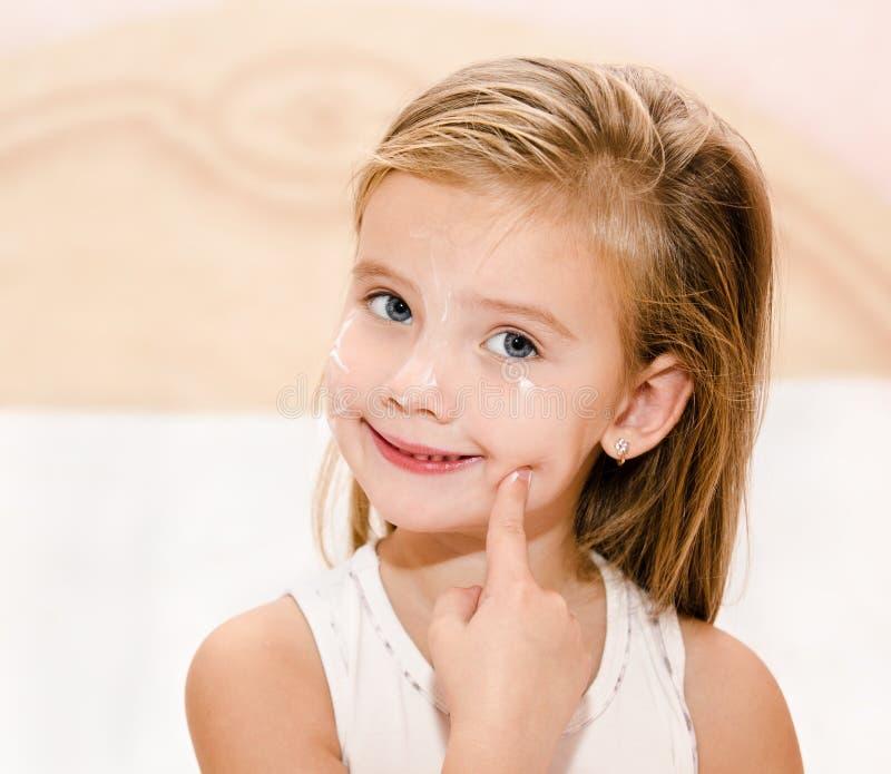 应用奶油的逗人喜爱的小女孩 免版税库存照片