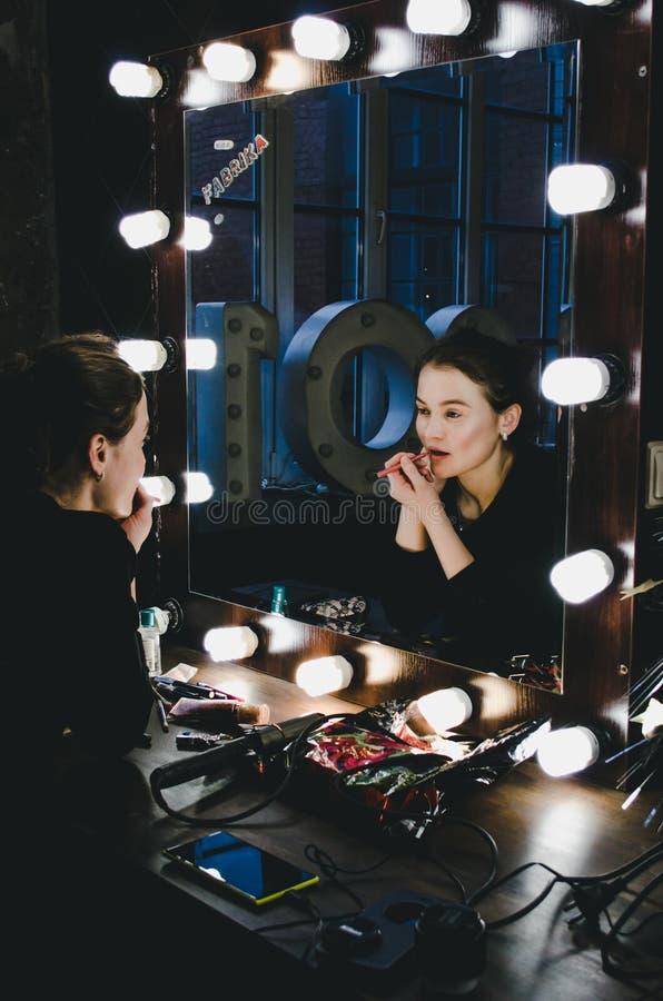 应用她的构成嘴唇的年轻美丽的妇女,注视着在镜子,坐椅子剧院化装室与 免版税库存照片
