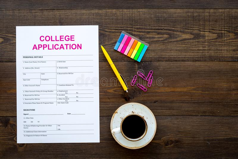 应用学院 在咖啡杯附近的空的学院在黑暗的木背景顶视图的申请表和文具复制 免版税库存图片