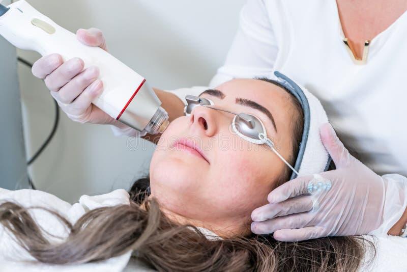 应用射频microneedling的handpiece的美容师于加强治疗的皮肤的妇女的面孔在秀丽诊所 图库摄影