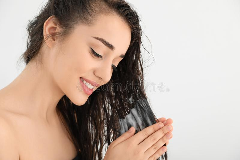 应用护发素的美丽的年轻女人反对白色背景 库存照片