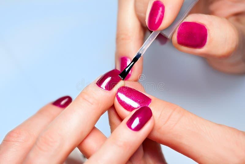 应用指甲的妇女于手指钉子 免版税库存照片
