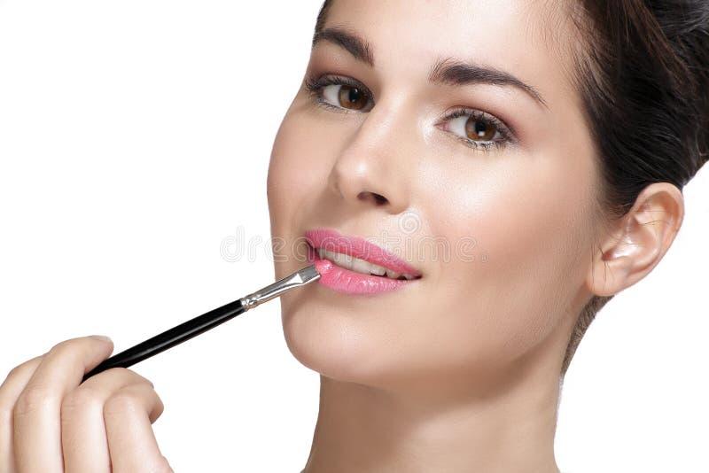 应用有刷子的美丽的少妇唇膏 免版税图库摄影