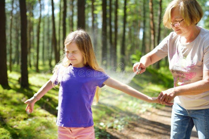 应用杀虫剂的中年妇女于她的孙女在森林远足美好的夏日前 保护的孩子从 图库摄影