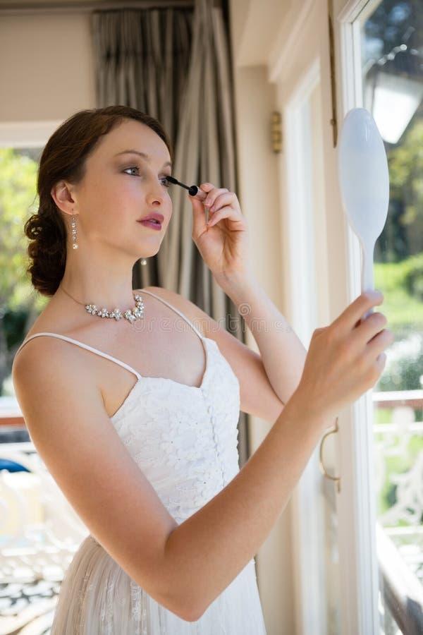 应用染睫毛油的美丽的新娘,当调查手镜由窗口时 库存图片