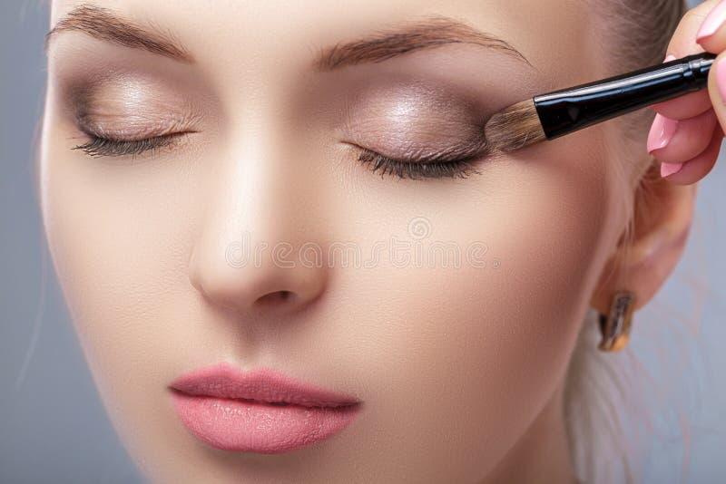 应用棕色眼影的美丽的妇女使用构成刷子 蓝眼睛的构成 免版税库存图片