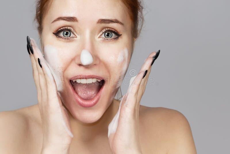 应用洗涤的快乐的笑的女孩画象泡沫在她的面孔 与引人注目的外观的可爱的妇女红头发人 ?? 库存图片