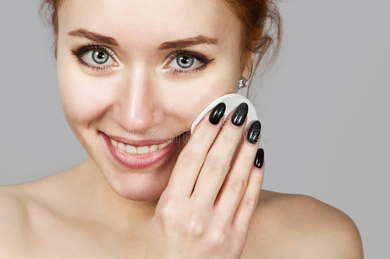 应用洗涤的快乐的笑的女孩画象泡沫在她的面孔 与引人注目的外观的可爱的妇女红头发人 ?? 免版税库存照片