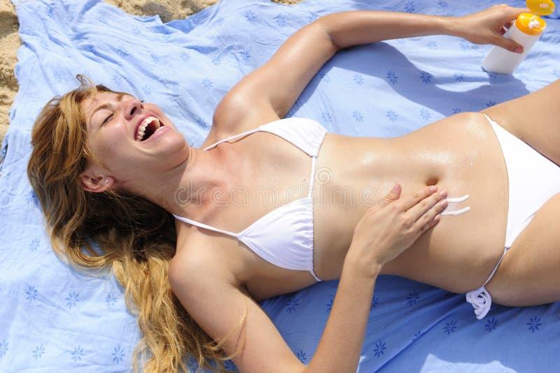 应用海滩化妆水晒黑妇女 免版税库存图片