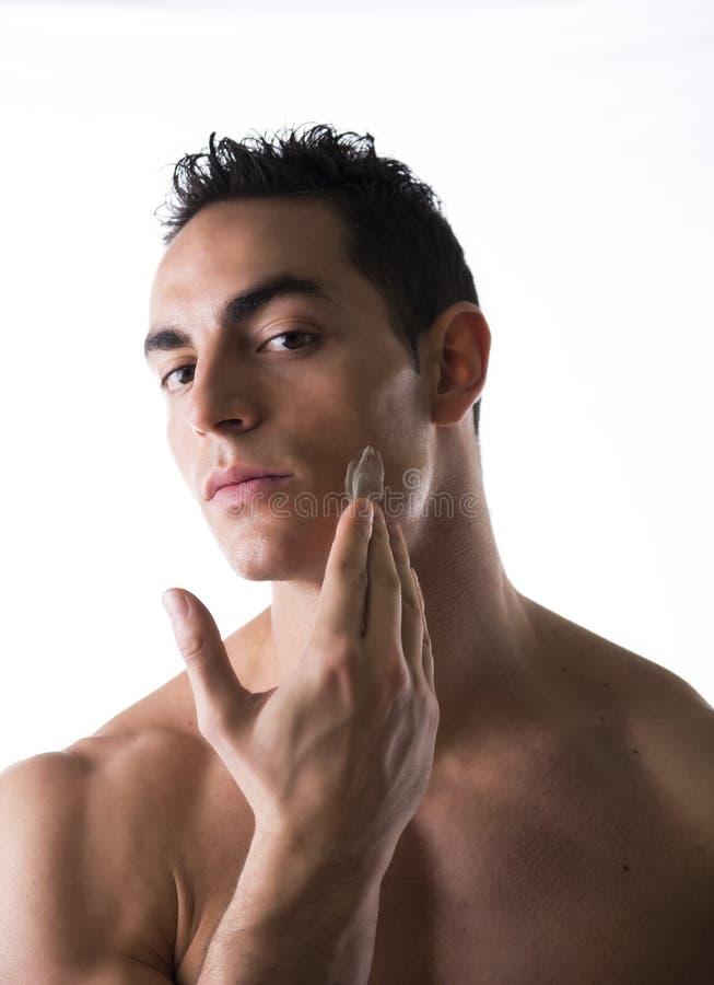 应用润湿的奶油的英俊的年轻人 免版税库存图片