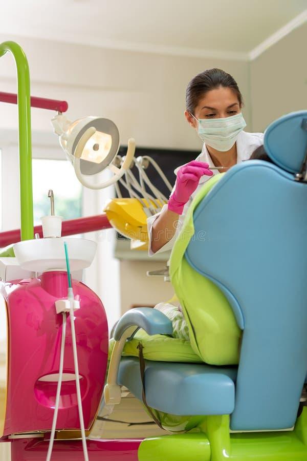 应用牙齿仪器的被集中的严肃的深色头发的女性牙医 库存图片