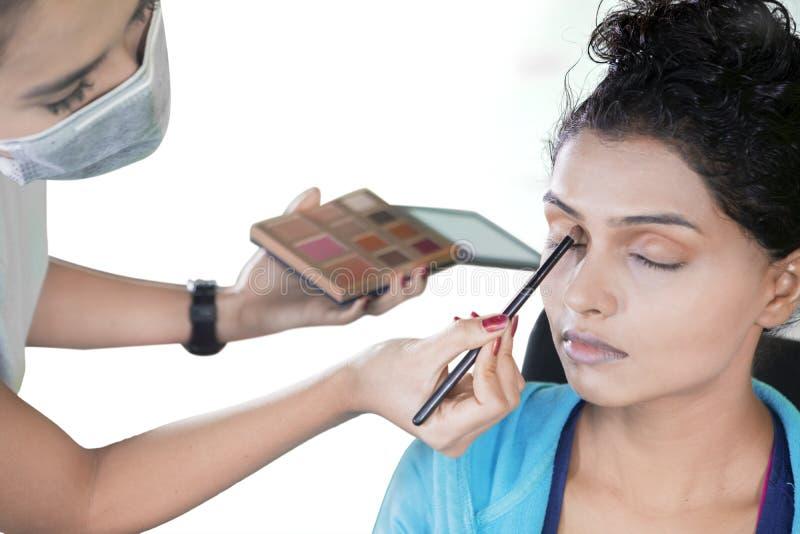 应用眼影膏的化妆师于她的客户眼睛 库存照片