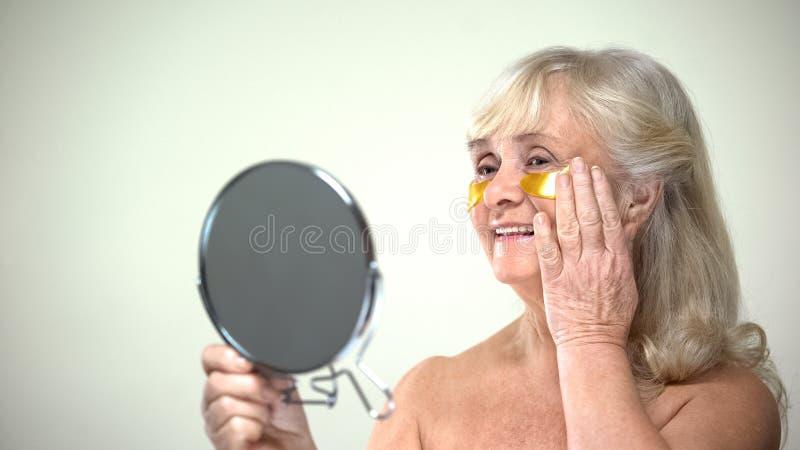应用眼睛补丁的快乐的微笑的夫人看在镜子,防皱疗法 库存图片