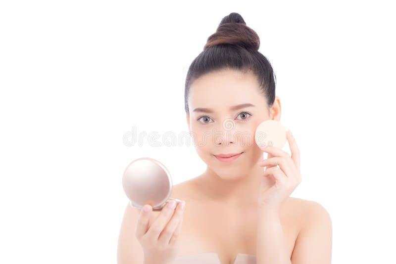 应用粉扑的美丽的亚裔妇女画象在化妆用品面颊构成,女孩秀丽有面孔微笑的被隔绝 库存照片
