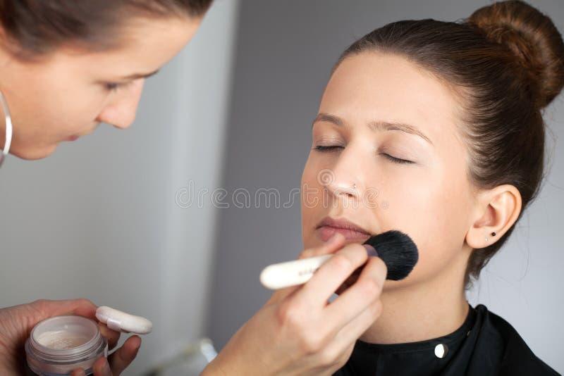 应用粉末的化妆师 免版税库存图片