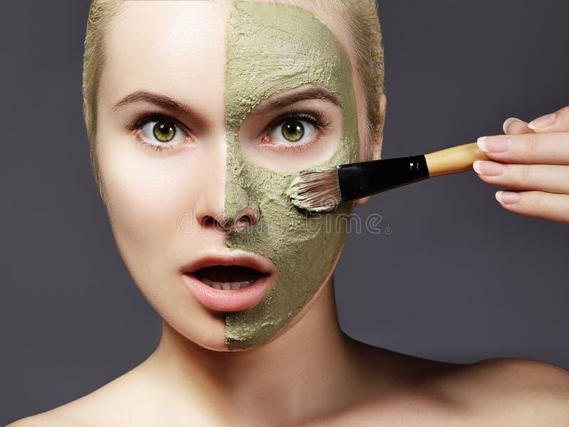 应用绿色面部面具的美丽的妇女 秀丽治疗 温泉女孩特写镜头应用与刷子的黏土面部面具 免版税库存图片