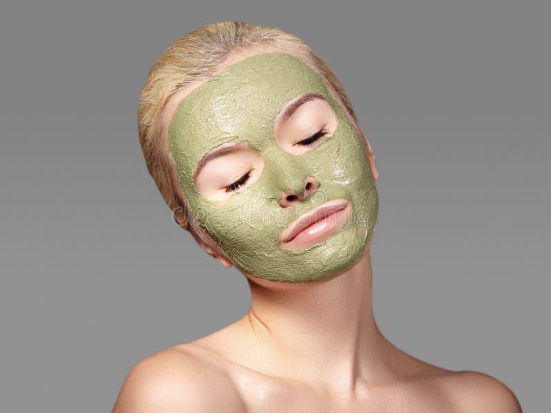 应用绿色面部面具的美丽的妇女 秀丽治疗 温泉女孩特写镜头画象应用黏土脸面护理面具 免版税库存照片