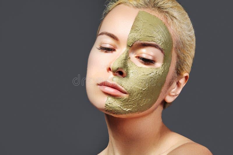 应用绿色面部面具的美丽的妇女 秀丽治疗 温泉女孩特写镜头画象应用黏土脸面护理面具 免版税库存图片