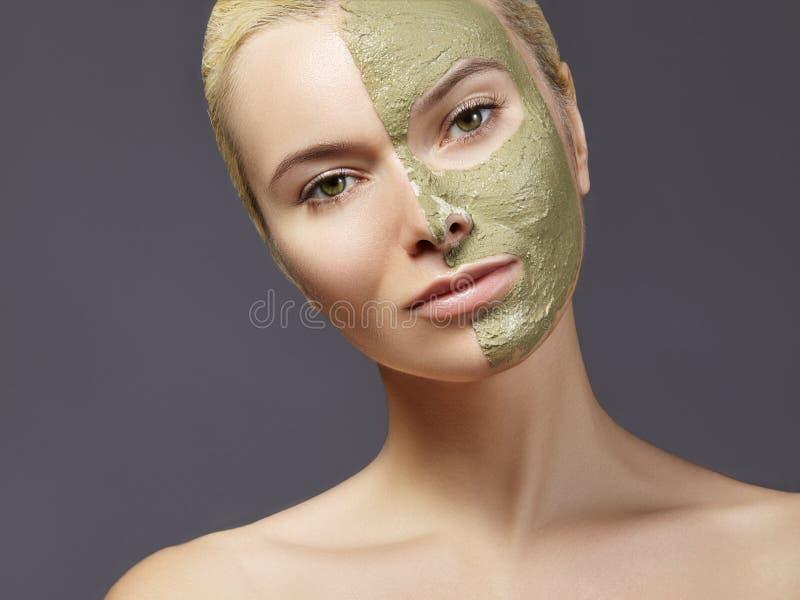 应用绿色面部面具的美丽的妇女 秀丽治疗 温泉女孩特写镜头画象应用黏土脸面护理面具 库存图片