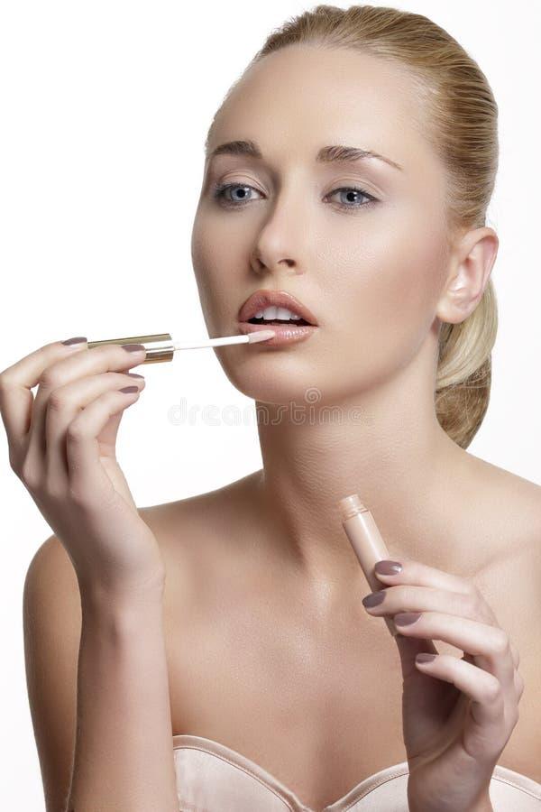 应用美丽的光泽嘴唇妇女年轻人 免版税库存图片