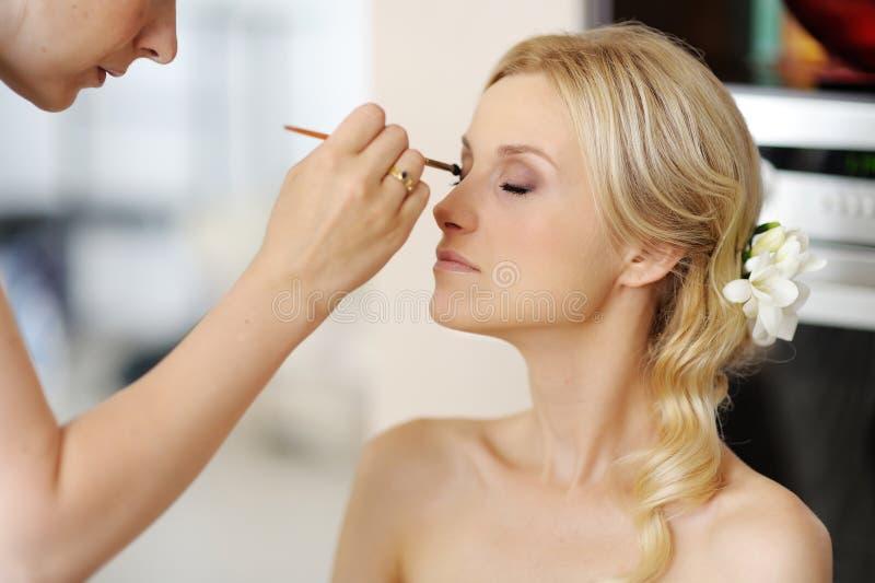 应用美丽的新娘做婚姻的年轻人 免版税库存照片