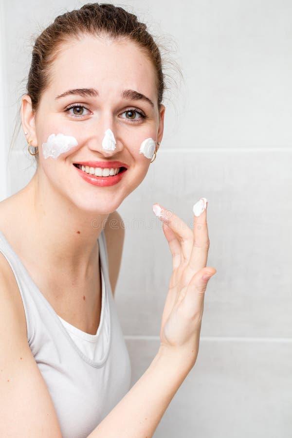 应用询问的skincare的紧张美丽的妇女润湿的面霜 库存图片