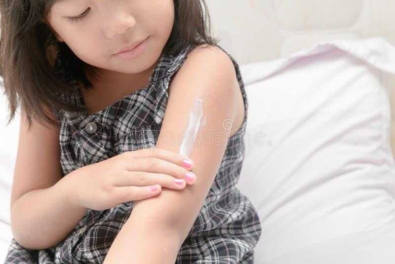 应用身体在她的胳膊的小女孩化妆水奶油 图库摄影