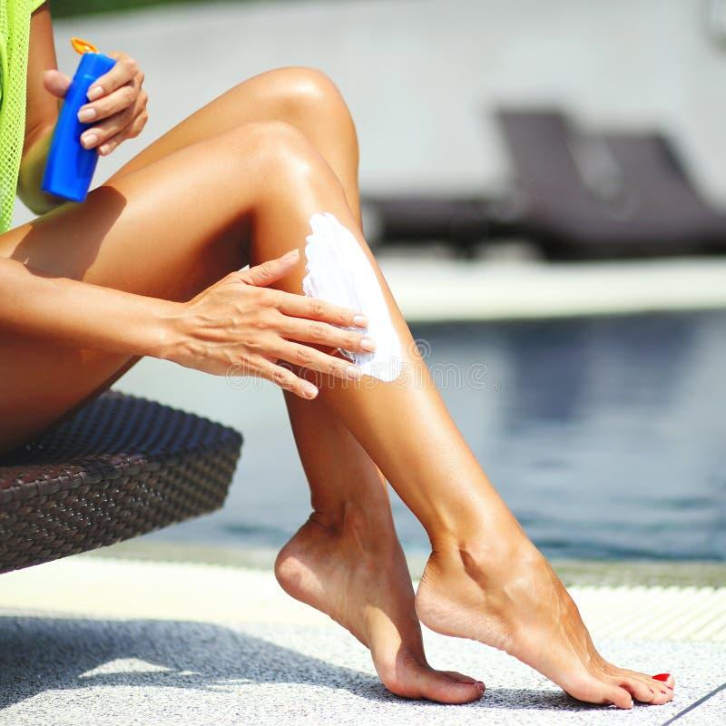 应用遮光剂化妆水的愉快的少妇 图库摄影