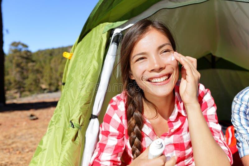 应用遮光剂的野营的妇女晒黑在帐篷的奶油 免版税库存图片