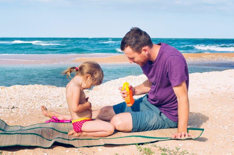 应用遮阳纸奶油的父亲于他的女儿 免版税库存图片