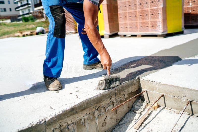 应用防水的密封胶的工作者在建造场所 库存照片