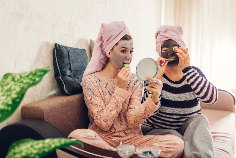 应用面膜和黄瓜在眼睛的母亲和她的成人女儿 获得的妇女在家使和乐趣变冷 免版税库存照片