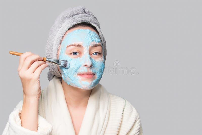 应用面部黏土面具的妇女在温泉沙龙或在家,skincare题材 面膜,温泉与拷贝空间的秀丽治疗 库存图片