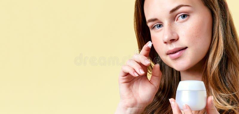 应用面霜,拿着白色奶油色瓶和调查照相机的年轻可爱的红头发人妇女 库存照片
