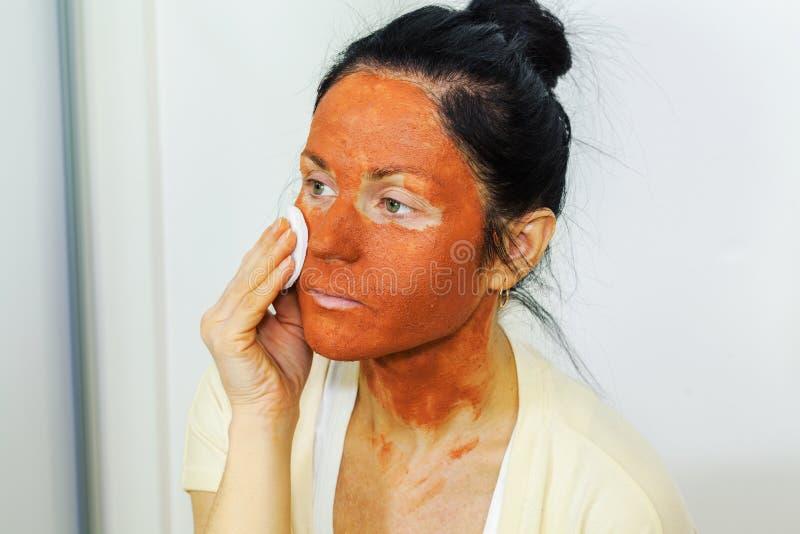 应用黏土泥面具的妇女于她的面孔 免版税库存图片