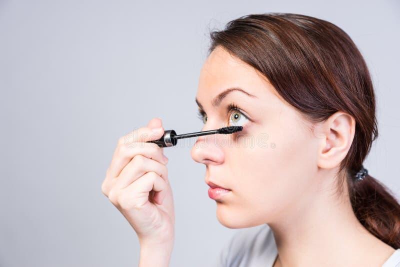 应用黑暗的染睫毛油的可爱的妇女 免版税库存照片