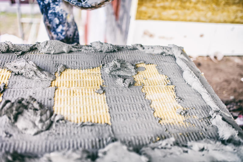 应用黏着性材料和灰浆在为修造门面使用的物质羊毛绝缘材料盘区的工作者  免版税库存图片