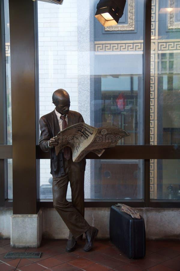 底特律,密执安,美国-第22, 2018年:读报纸的一个人的雕象在底特律的平台 库存照片