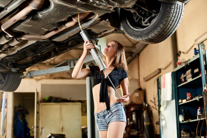 底视图美好的模型坦率地穿戴了与工具在汽车下 免版税库存照片